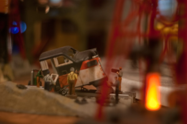 Diorama of workers scrapping a diesel locomotive next to a simulated oil well fire