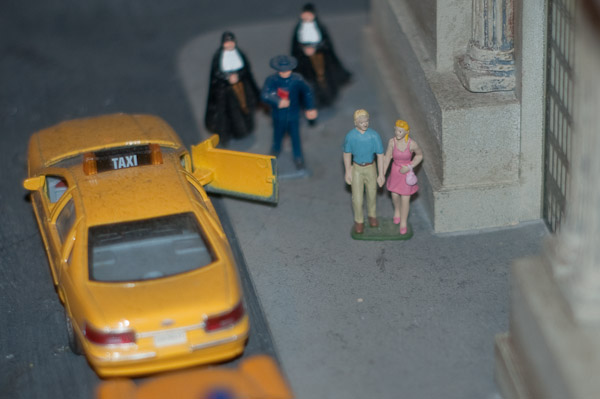Scale figures and taxi next to model of Grand Central Terminal